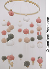 Details of newborn baby room. Toys above the baby crib. Hanging carousel of soft colorful balls for the child.