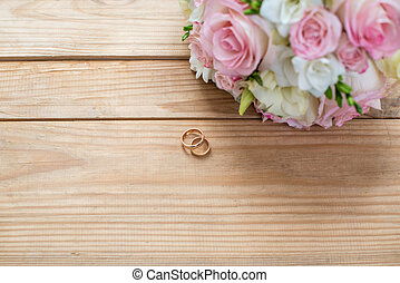 Details of the morning of the wedding day. two gold wedding rings are on the brown wood table