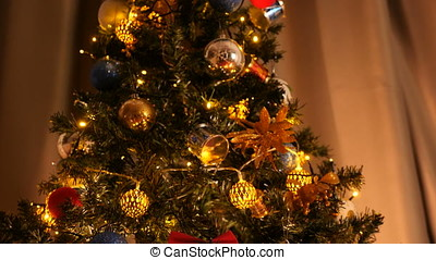 Details on beautiful christmas tree with blinking garlands...