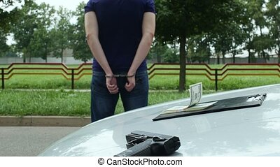 detained criminal in shackles stands near a stolen auto -...