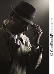 Detective adjusting his hat standing in the dark, film noir