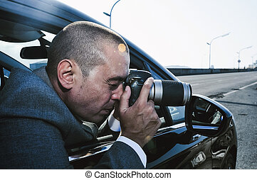 detective or paparazzi taking photos from a car