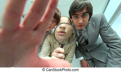 Group of business people looking through magnifying glass