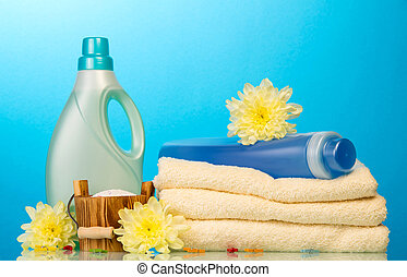 Detergent in bottles and towels isolated on blue background