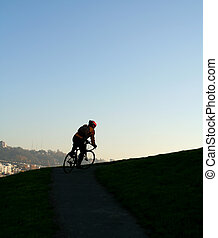A man climbing uphill on a bicycle showing effort and determination