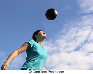 Determination - Girl heading a soccerball. Funny expression!