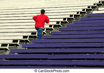 Determination - Teen running up some bleachers in a stadium.