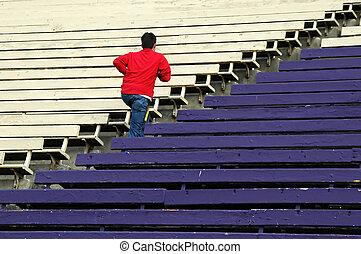 Teen running up some bleachers in a stadium.