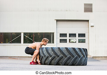 Determined Athlete Lifting Large Tire - Side view of...