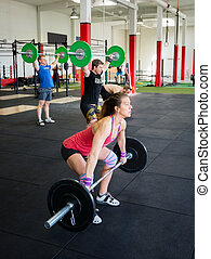 Determined Athletes Lifting Barbells In Gym