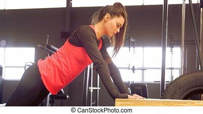 Determined beautiful Caucasian woman doing push-ups on ...