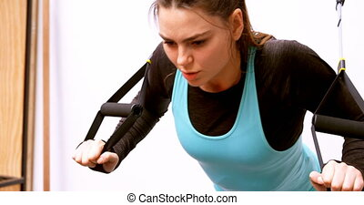 Determined beautiful Caucasian woman exercising in fitness ...
