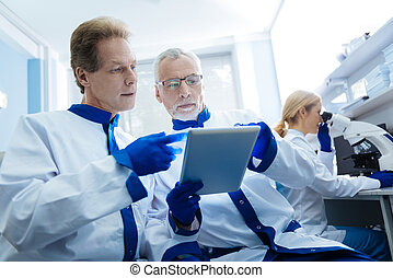 Determined biologists discussing gene results displayed on a...