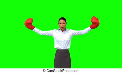 Determined businesswoman gesturing with boxing gloves on...