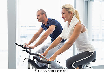 Determined couple working on exercise bikes at gym