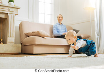 Determined emotional baby crawling while his father looking at him