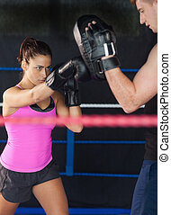 Determined female boxer practicing in the boxing ring