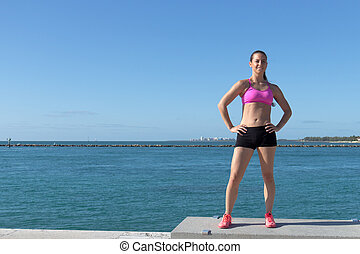 Determined, fit hispanic woman by the ocean