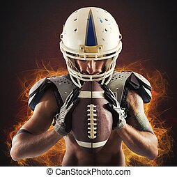 Determined football player - Football player holding ball in...