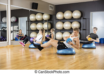 Determined Friends Exercising With Medicine Ball In Gym -...