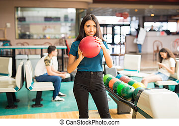 Determined Girl Getting Ready To Throw Bowling Ball At Alley