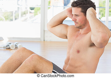 Determined man doing abdominal crunches at gym