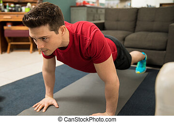 Determined man working out at home