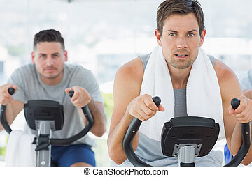 Determined men using exercise bikes