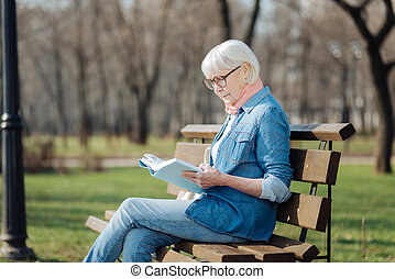 Determined old woman reading a book