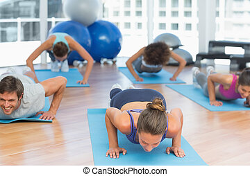 Determined people doing push ups in fitness studio -...
