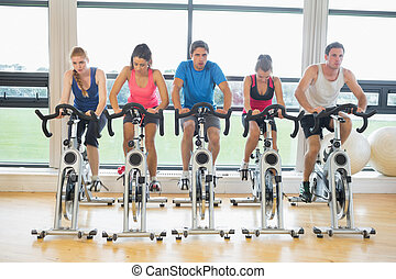 Determined people working out at spinning class in gym -...