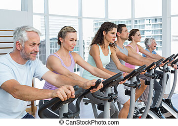 Determined people working out at spinning class - Side view...