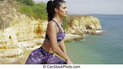 Determined sportswoman stretching on beach - Serious young...