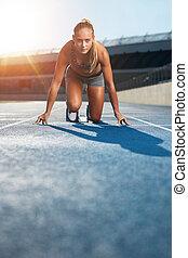 Determined sprinter at starting block