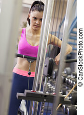 Determined woman doing exercises in gym on lat machine