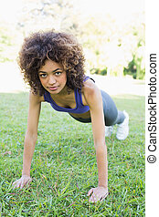 Determined woman doing push ups in park