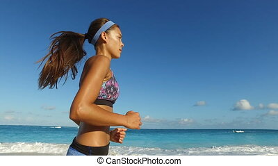 Determined Woman Jogging On Beach Against Blue Sky - Healthy...