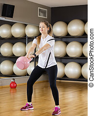Determined Woman Lifting Kettlebell In Health Club