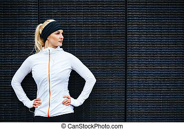 Portrait of determined young sports woman looking away while standing against a dark wall outdoors.