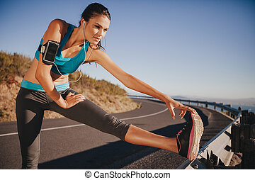 Determined young woman warming up before a run
