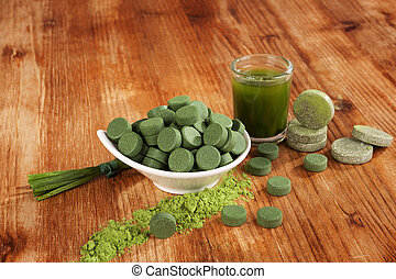 Chlorella, spirulina and wheat grass pills, ground powder on wooden background. Detox and healthy living.
