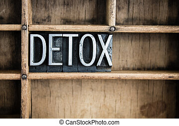 """The word """"DETOX"""" written in vintage metal letterpress type in a wooden drawer with dividers."""