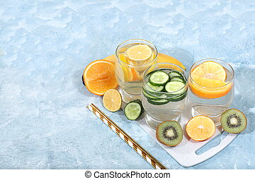 Detox diet and weight loss concept. Fruit drink and ingredients, summer tropical fruits and cocktails on a blue table, top view, healthy and natural food, source of vitamin C,
