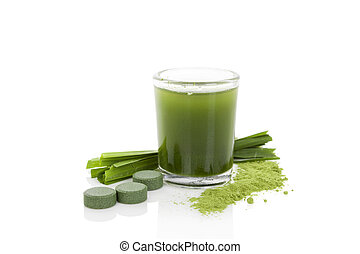 Detox. Green dietary supplement spirulina, chlorella and wheatgrass pills, grass blades and green juice isolated on white background. Healthy living.