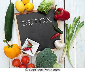 Detox handwritten on a chalkboard surrounded by fresh vegetables