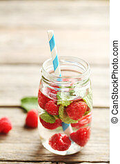 Detox water in bottle with berries on wooden table