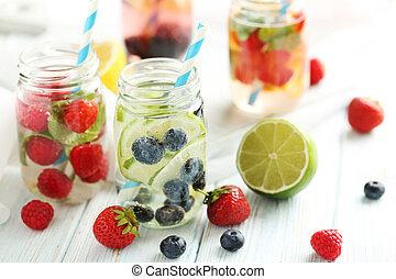 Detox water in bottles with berries on wooden table