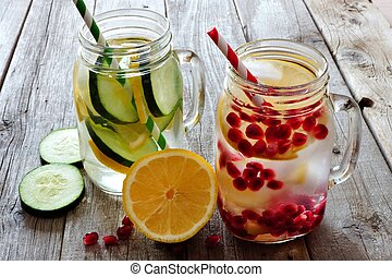 Detox water in mason jar glasses with lemon, cucumber and pomegranate against a rustic wood background
