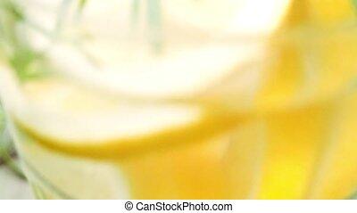 Detox water lemon cocktail on wooden table.
