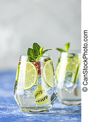 Detox water or martini tonic cocktail with kiwi, lime and ...